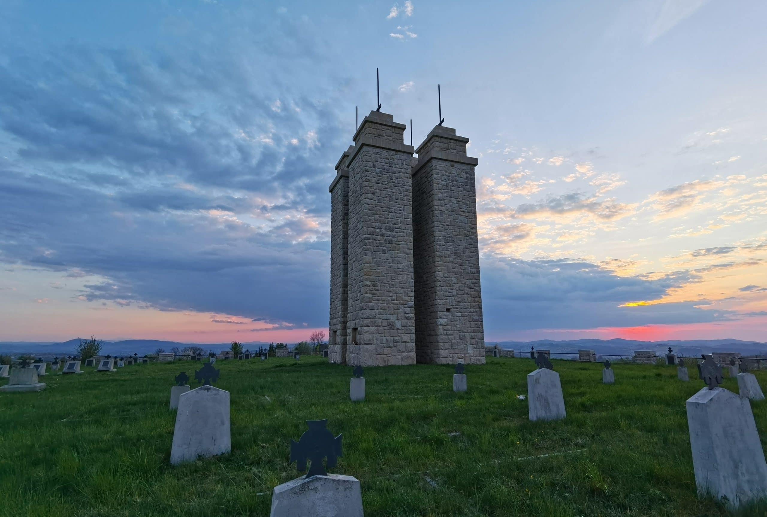 Cmentarz wojenny 118 w Staszkówce na tle zachodzącego słońca.
